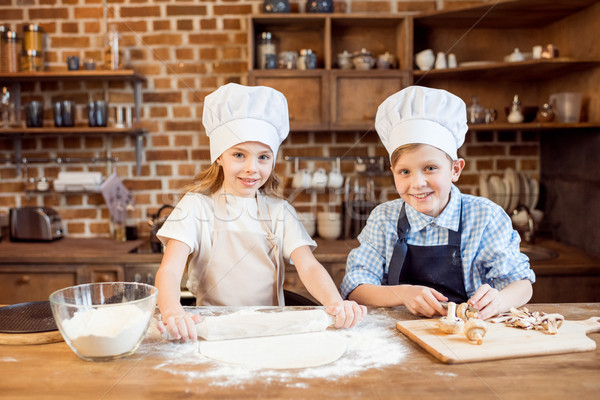 children making pizza dough and preparing pizza ingredients in kitchen  Stock photo © LightFieldStudios