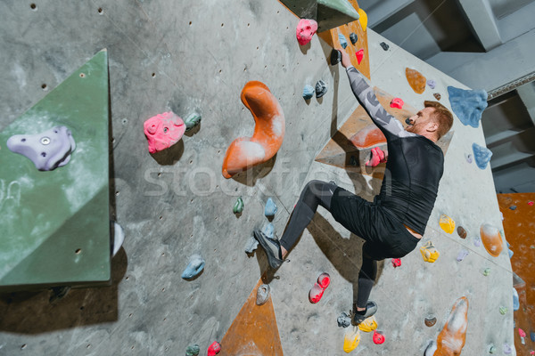 Man climbing wall with grips Stock photo © LightFieldStudios