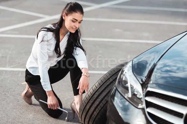 Woman changing car tire Stock photo © LightFieldStudios