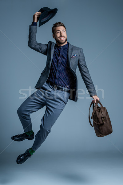 Homme costume sautant up souriant jeune homme Photo stock © LightFieldStudios