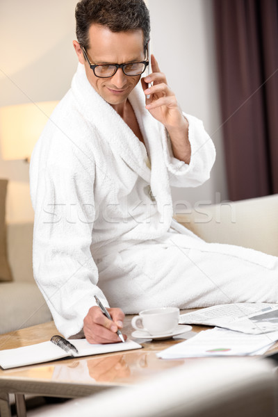 Businessman in bathrobe taking notes Stock photo © LightFieldStudios