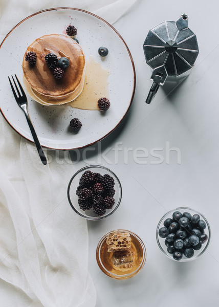 top view of tasty breakfast with pancakes, berries, honey and coffee on grey  Stock photo © LightFieldStudios