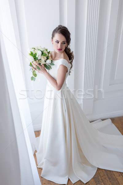 Stock photo: young bride posing in elegant dress with wedding bouquet