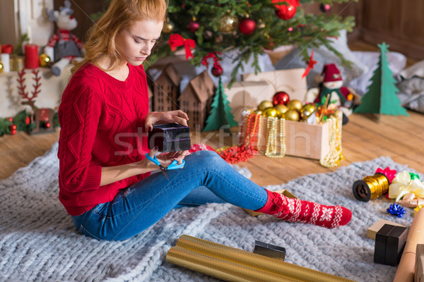 Girl wrapping gift box Stock photo © LightFieldStudios