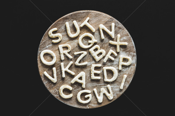 Top view of edible letters from dough on wooden cutting board, baking cookies concept Stock photo © LightFieldStudios