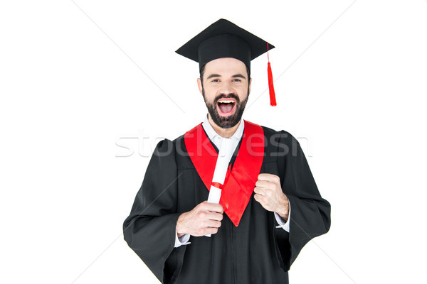 Excited young man in graduation hat holding diploma and triumphing on white Stock photo © LightFieldStudios
