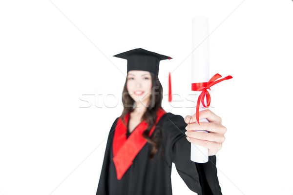 Close-up view of smiling student in graduation gown holding diploma on white   Stock photo © LightFieldStudios