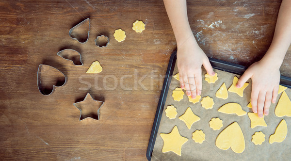 top view of child with raw shaped cookies on baking tray and cookie cutters on wooden table  Stock photo © LightFieldStudios