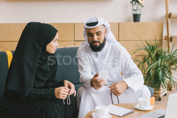 muslim man showing smartphone to woman Stock photo © LightFieldStudios