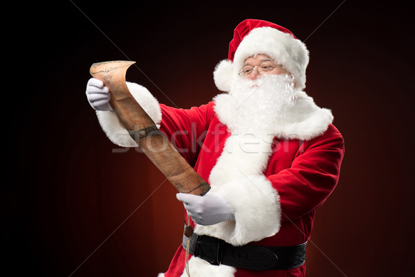 Santa Claus reading wishlist Stock photo © LightFieldStudios