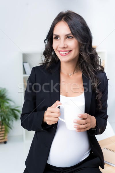 pregnant businesswoman with cup of hot drink Stock photo © LightFieldStudios