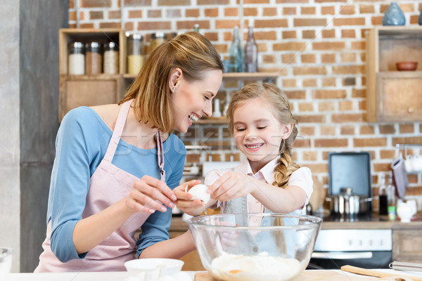 Happy mother and daughter preparing dough for home baking  Stock photo © LightFieldStudios