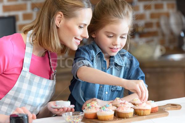 Stock photo: side view of daughter and mother decorating cupcakes with confetti