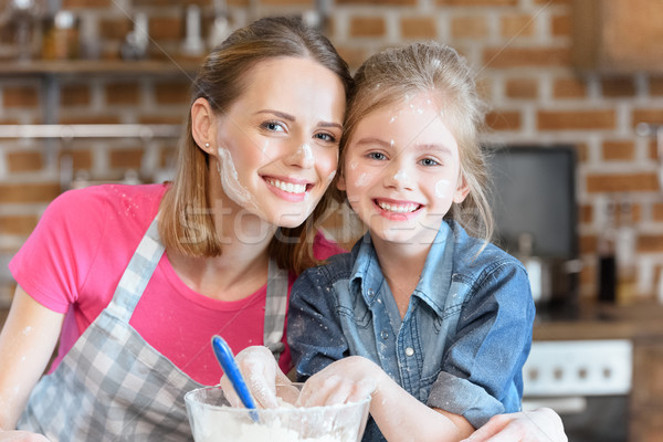 portrait of smiling mother and daughter cooking at home Stock photo © LightFieldStudios