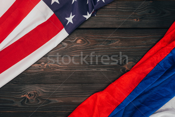 top view of american and russian flags on dark wooden tabletop Stock photo © LightFieldStudios