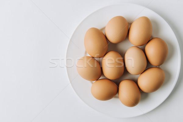 brown eggs laying on white plate on white background  Stock photo © LightFieldStudios