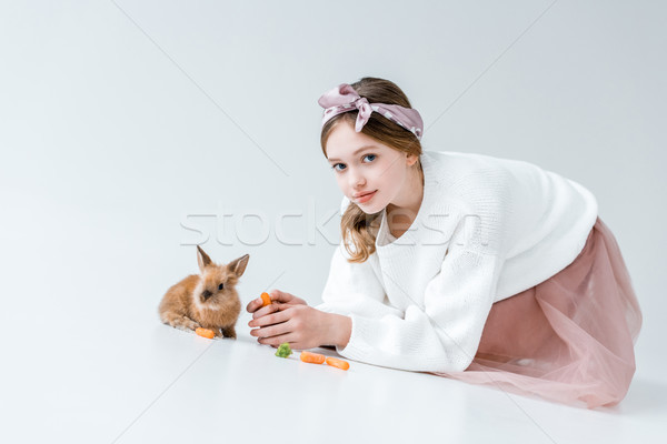 adorable girl looking at camera while feeding rabbit isolated on white Stock photo © LightFieldStudios