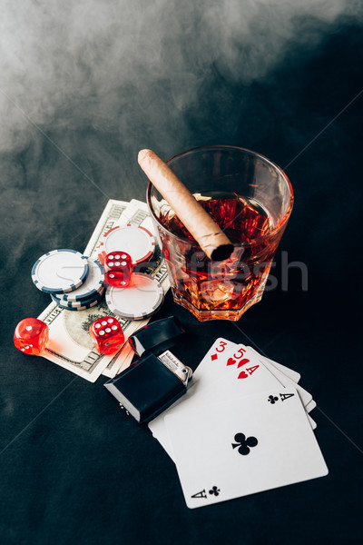 Smoke over whiskey and cigar on table with chips and money Stock photo © LightFieldStudios