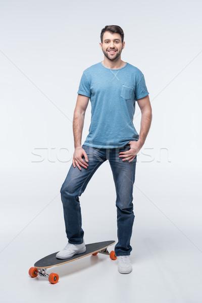 smiling man standing with skateboard on white Stock photo © LightFieldStudios