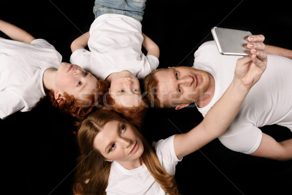 Stock photo: high angle view of family taking selfie on smartphone isolated on black