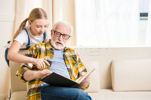 Cute little girl with grandfather in eyeglasses reading book together  Stock photo © LightFieldStudios