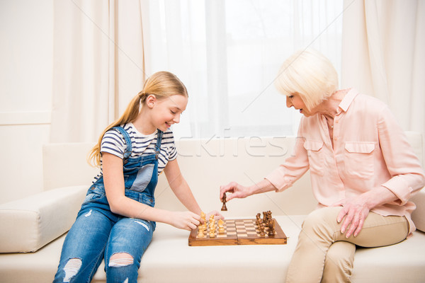 Happy girl with grandmother sitting on sofa and playing chess Stock photo © LightFieldStudios