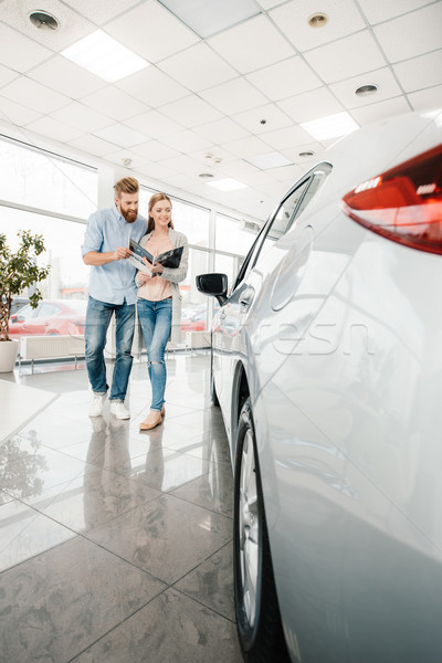 Happy couple holding catalog and choosing car in dealership salon    Stock photo © LightFieldStudios