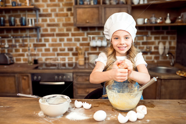 little girl in chef hat making dough for cookies Stock photo © LightFieldStudios