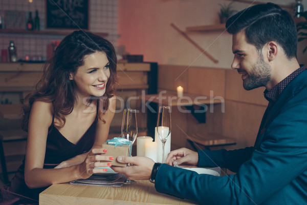 man presenting gift to girlfriend Stock photo © LightFieldStudios
