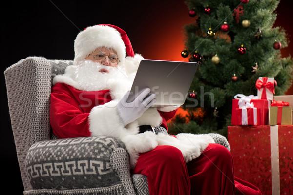 Papai noel usando laptop sessão cinza poltrona feliz Foto stock © LightFieldStudios