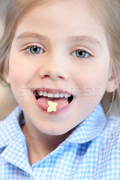 portrait of happy girl with piece of pastry on tongue Stock photo © LightFieldStudios
