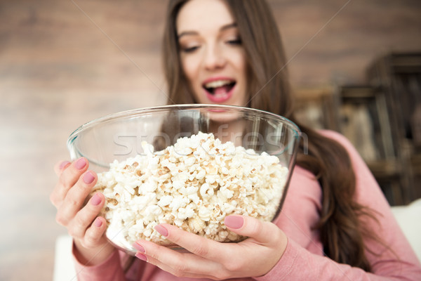 Close-up view of excited young woman holding glass bowl with popcorn Stock photo © LightFieldStudios