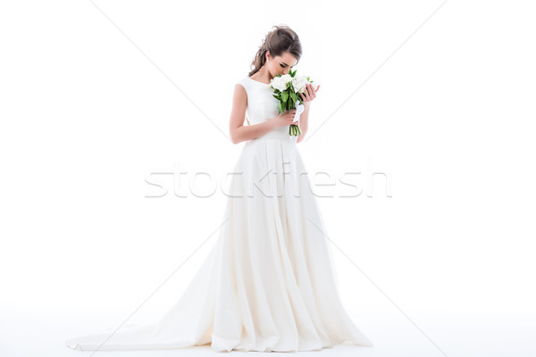 Stock photo: elegant bride posing in traditional dress and sniffing wedding bouquet, isolated on white
