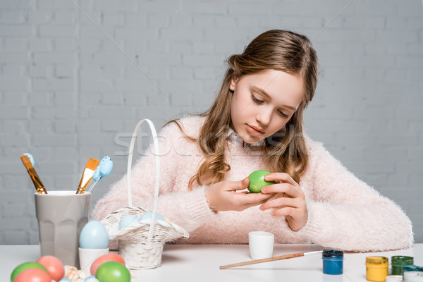 beautiful little girl holding easter egg while sitting at table with pants and brushes Stock photo © LightFieldStudios