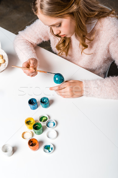 beautiful focused teenage girl painting easter egg at table Stock photo © LightFieldStudios