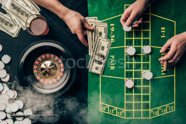 Men placing a bet on casino table with roulette Stock photo © LightFieldStudios