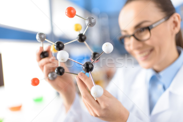 smiling scientist holding molecular model in laboratory, focus on foreground Stock photo © LightFieldStudios