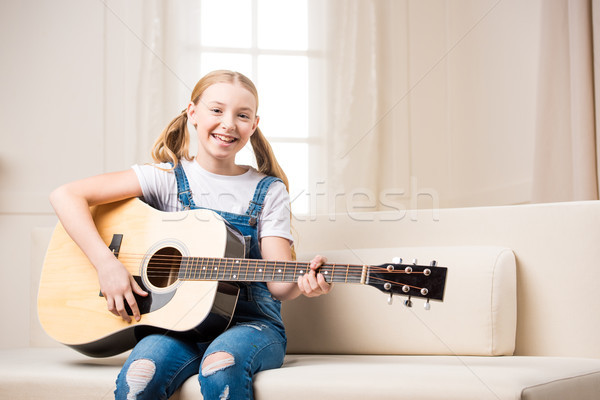 Cute smiling girl sitting on sofa and playing acoustic guitar Stock photo © LightFieldStudios