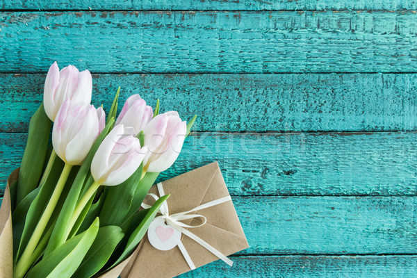 Stock photo: light pink tulips bouquet and envelope on turquoise wooden tabletop with copy space, wedding cards f