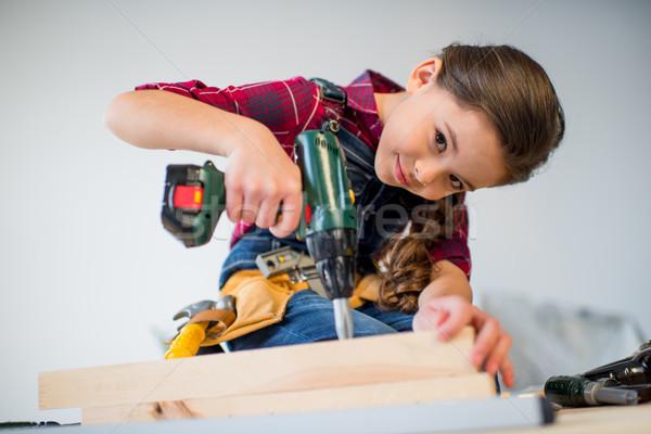 Girl drilling plank Stock photo © LightFieldStudios