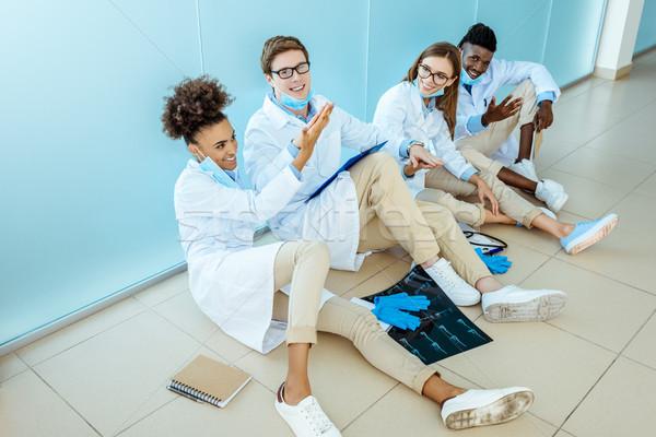 smiling doctors sitting in hospital corridor Stock photo © LightFieldStudios
