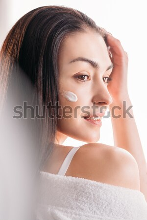 Young woman with cream applied to face Stock photo © LightFieldStudios