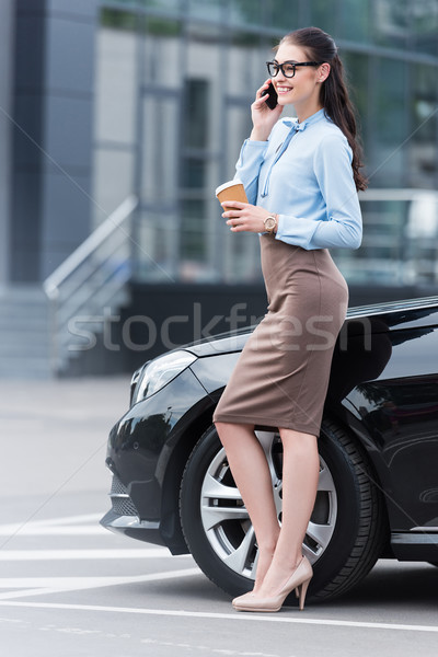 Stock photo: businesswoman talking on smartphone with coffee