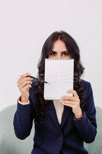 Femme d'affaires visage notepad jeunes pointant travaux Photo stock © LightFieldStudios