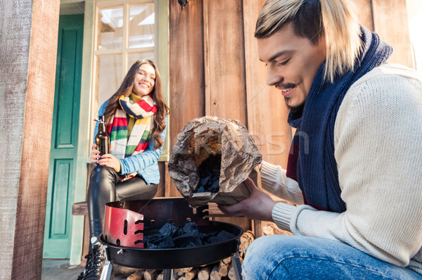 Smiling woman with beer bottle looking at handsome man filling grill with charcoal  Stock photo © LightFieldStudios