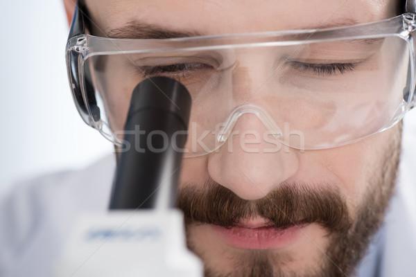 Hombre mirando microscopio primer plano vista joven Foto stock © LightFieldStudios
