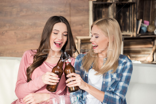Happy young women clinking beer bottles while sitting on couch Stock photo © LightFieldStudios