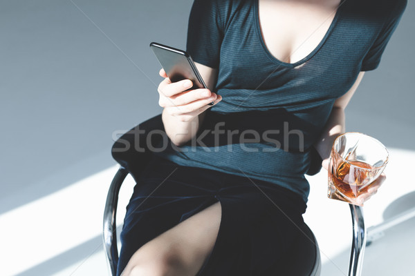 woman with smartphone and glass of whisky Stock photo © LightFieldStudios