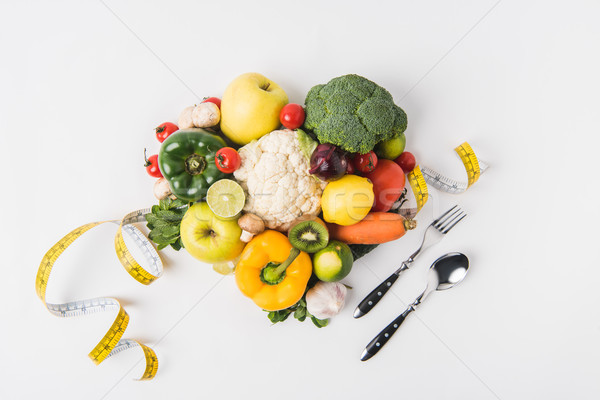 vegetables and fruits laying on white background with fork, spoon and measuring tape   Stock photo © LightFieldStudios