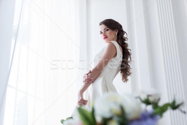 Brunette kaukasisch bruid trouwjurk venster bloemen Stockfoto © LightFieldStudios